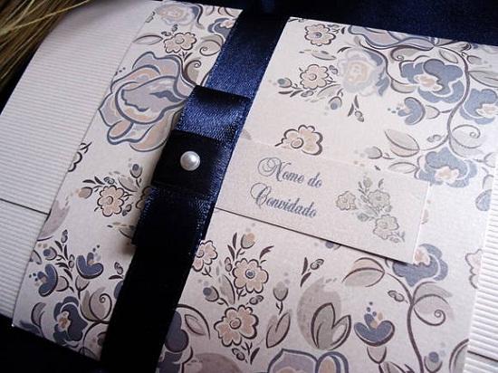 Convite de casamento com estampa preta, papel branco e fita azul
